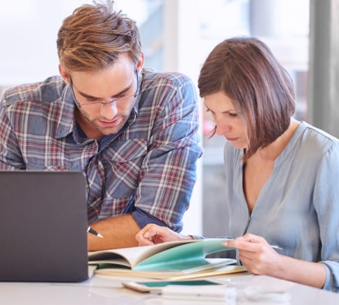 image of a male and female reviewing a Commercal Term-life Insurance policy while sitting in front of a computer in Franklin, TN