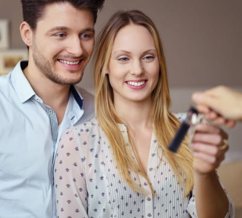 image of a couple receiving a set of keys, they take the key knowing that they are covered by the best Renters' Insurance polcy in Franklin, TN